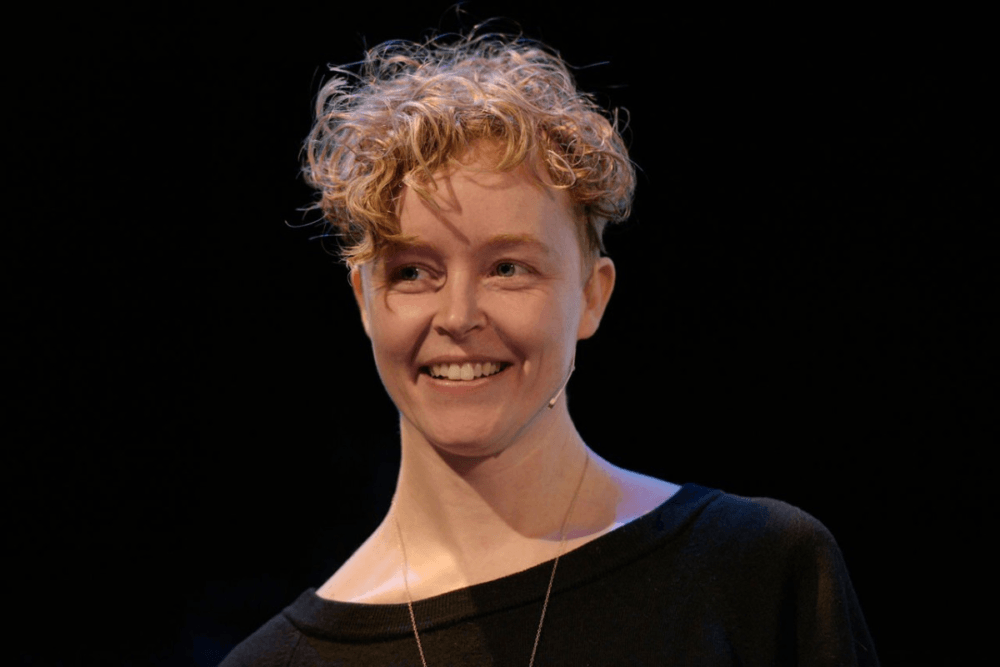 Close up of a young blonde woman with short, curly hair and a black shirt. She stands against a black background and smiles at something to the left of the camera.