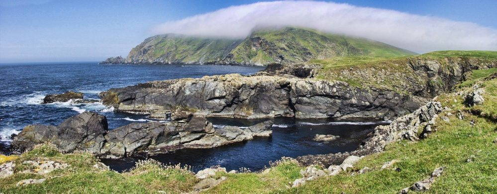 High rocks jut into the dark blue ocean. A mist hangs above the furthest cliffs. Sparse green grass glrows in the foreground.