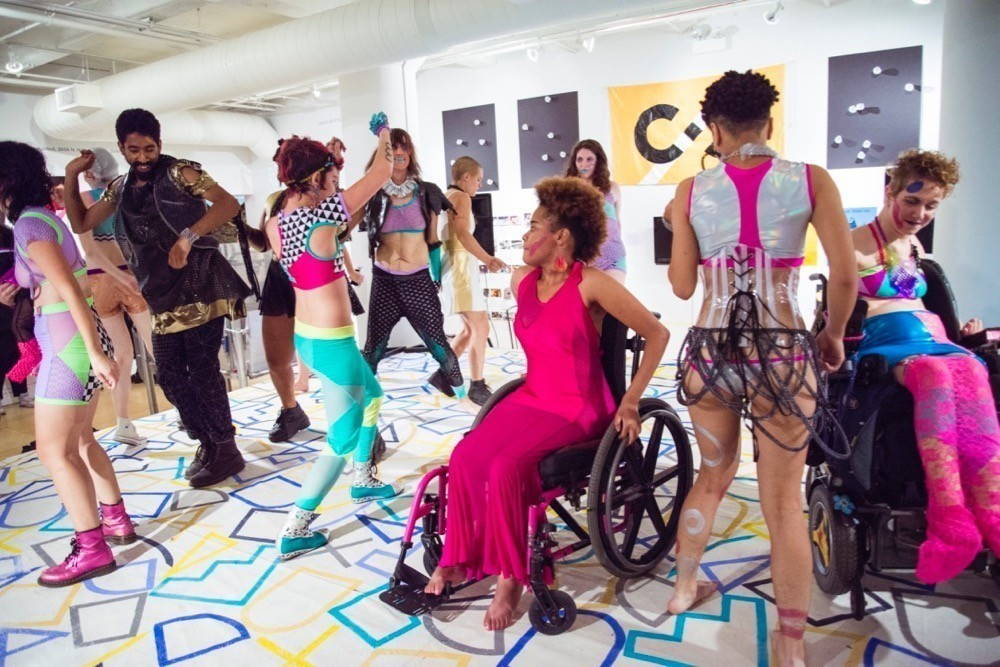 A group of people wearing colorful, unusual clothes - many of them plastic or plastic hybrid materials - dance and mingle on top of a colorful rug. In the foreground, two people using wheelchairs and wearing hot pink dresses and skirts are behind a third, wearing a corset made of clear plastic.