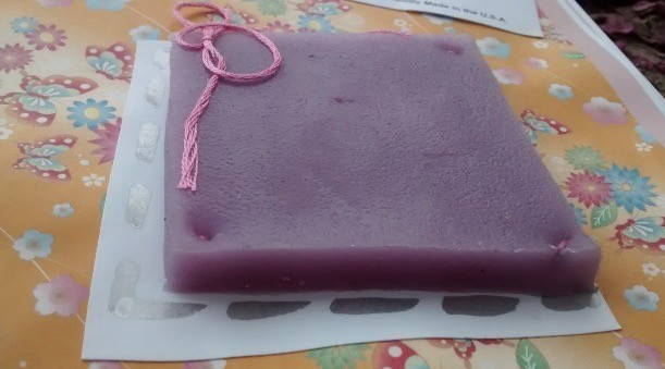 A photograph of a square of artificial skin, purple or dark pink in hue, with a visible, mottled texture and a pink ribbon tied to it