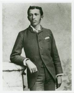 Black and white portrait of a W. E. B. Du Bois looking dignified in a checkered suit leading on his right elbow.