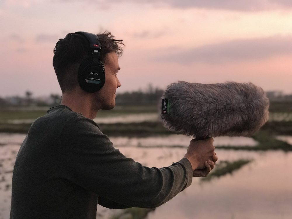 """A young man stands in front of a water landscape at sunset pointing a large microphone with a fluffy grey """"dead cat"""" windscreen off to the right to record environmental sounds."""