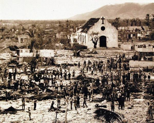 Sepia toned historical photograph of dozens of people stand in a village completely leveled by a hurricane except for a church which stands in front of a mountain in the background.