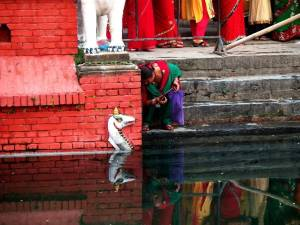 A woman sitting on steps washing dishes in a temple pool.