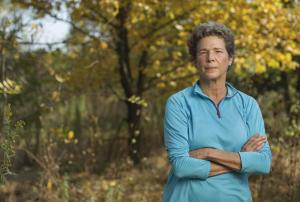 Tia Nelson poses folding her arms and wearing a light blue pullover in front of brown grass and yellow foliage.