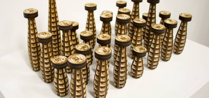 A series of differently shaped laser cut and engraved wood seals are arranged on a surface.