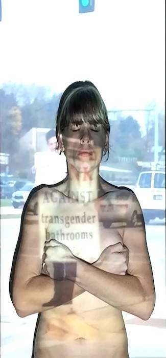 An image of rally protesting transgender people's use of bathrooms is superimposed over an image of the artist covering her breasts.