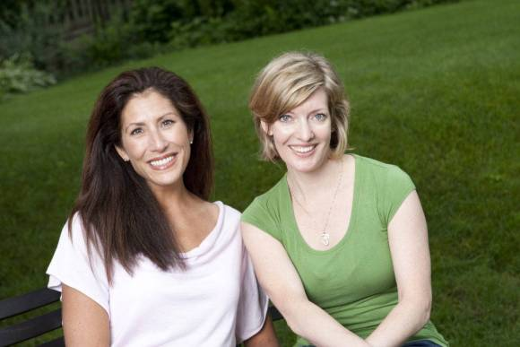 Two women smile at the camera while sitting in front of a green hillside.