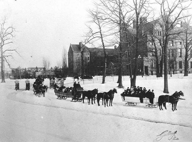Horses pull three sleighs filled with people over the snow.