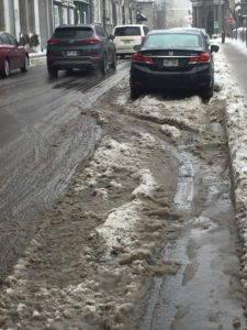 Cars drive through dirty slush on a city street