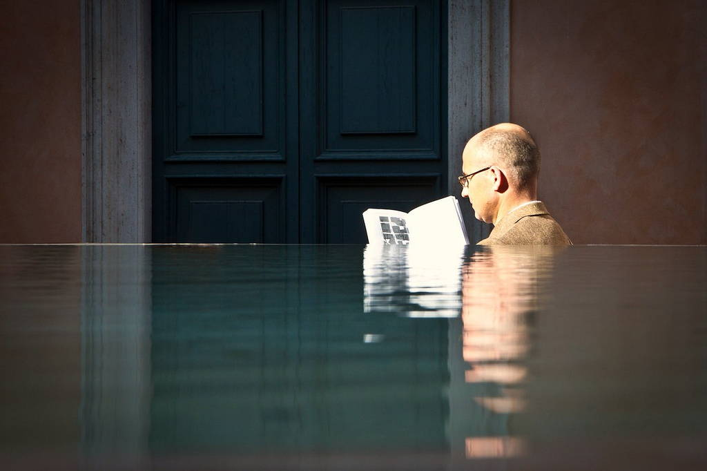 The head of a man wearing glasses and reading a book sticks out from behind a pool and is reflected in it.