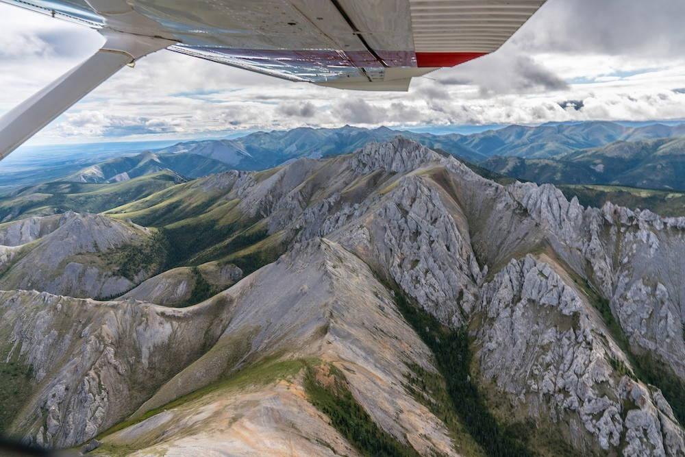 An aerial view of the Arctic National Wildlife Refuge with the wing of the airplane in view