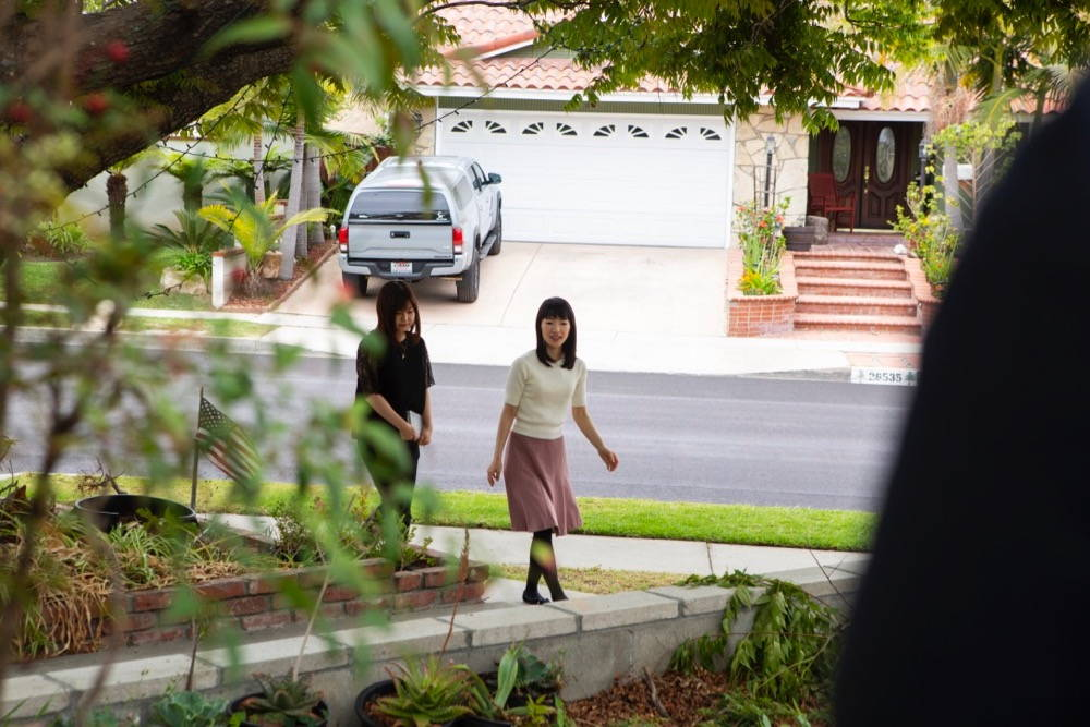 Marie Kondo and interpreter arrive at a suburban house, walking up the driveway