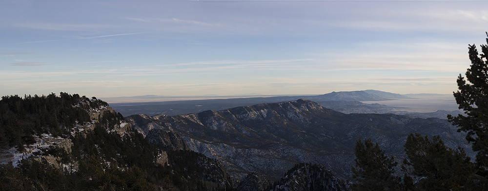 A dark mountain range under a blue sky