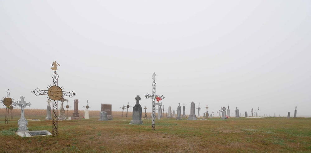 A cemetery's wrought-iron crosses mix with stone grave markers on a flat grassy and foggy plain under an overcast sky.
