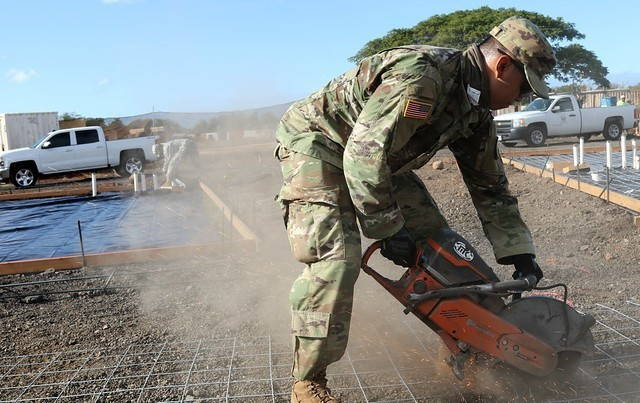 A soldier in green camouflage fatigues sends up sparks cutting into a metal grid on the ground with a large sawzall. Two white pickup trucks and another solider are in the background.