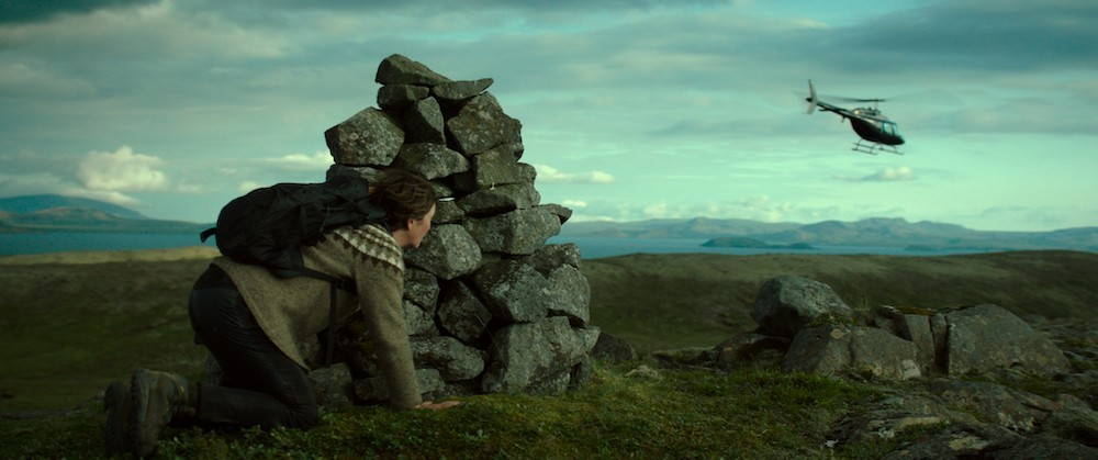 A woman peeks around a pile of stones at a helicopter flying away across a vast plain with mountains in the background.