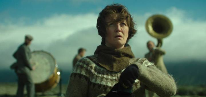 A woman in a brown sweater stand out on an open plain looking troubles while a three-piece band plays in the background.
