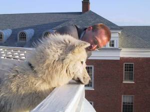 A white canid and a human being lean on a rooftop balcony together