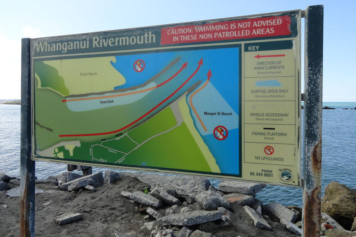 A sign with information and advisories about the Whanganui Rivermouth