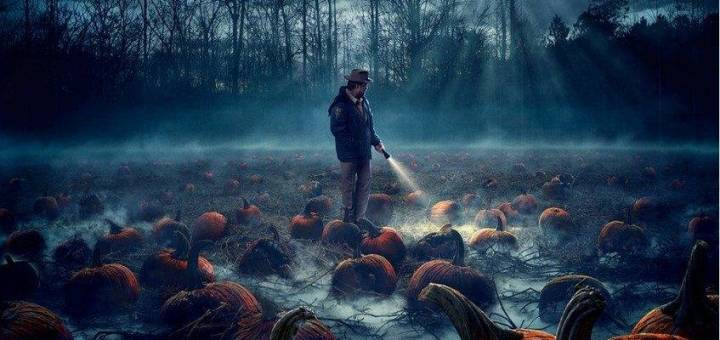 Man with flashlight in a field of rotted pumpkins at night.