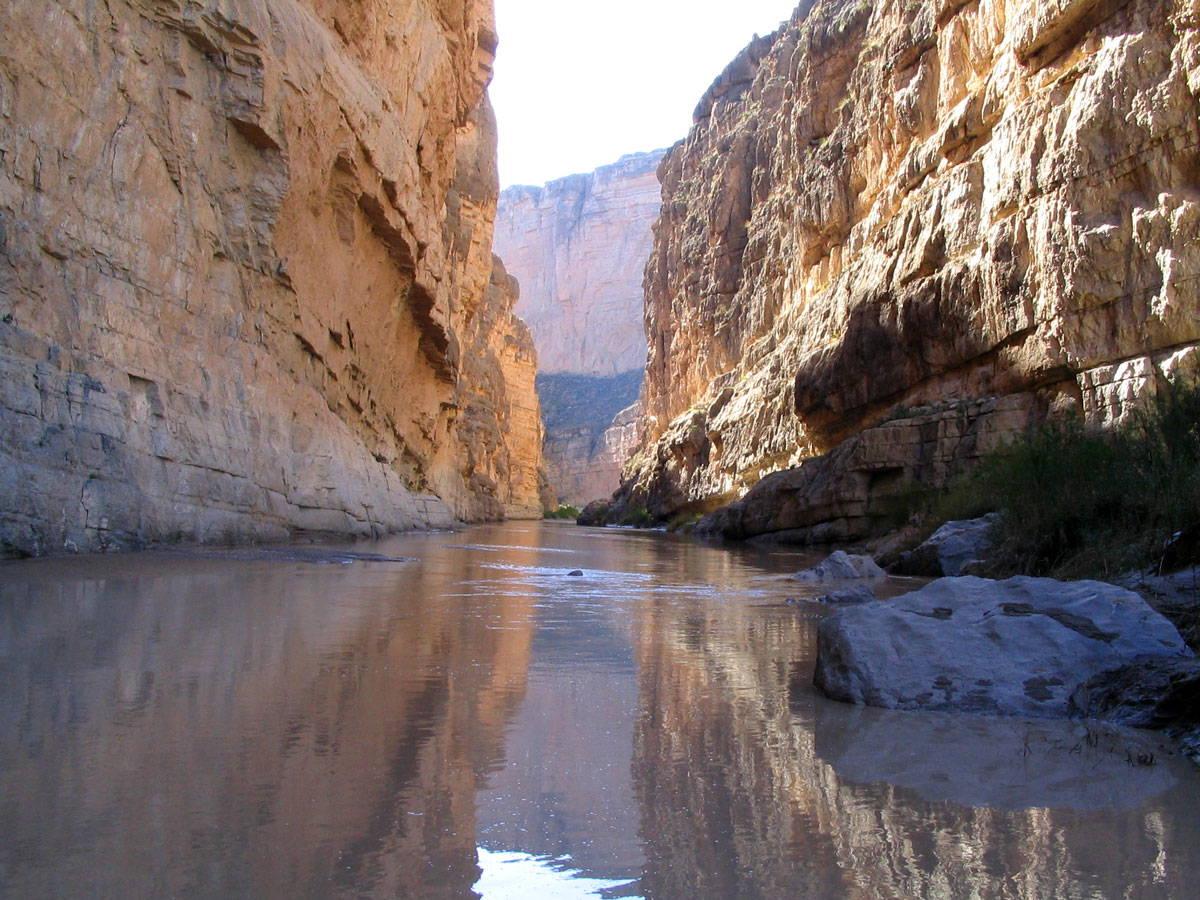 A river runs through a narrow gap in tall rock canyons