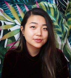 Christine Liu's headshot, a photograph of her against a background of painted flowers