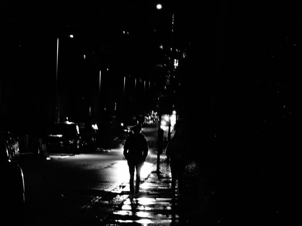 A dark city street with the shape of a person walking dimly illuminated by car headlights
