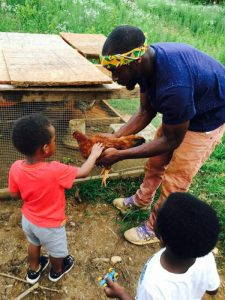 Kamal Bell showing a chicken to two small children at Sankofa Farms