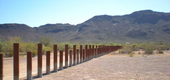 Waist-high, metal bollards stretch across the desert toward chaparral hillsides in the background.