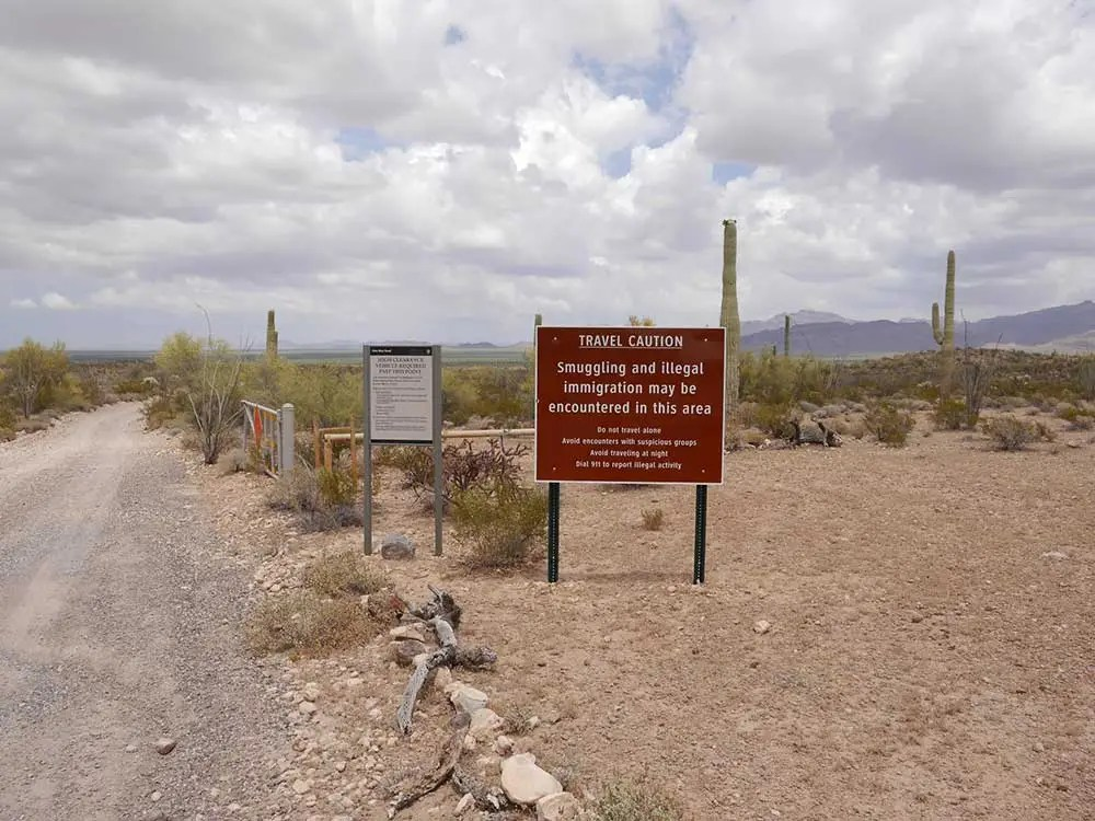 """Signs warning of """"smuggling and illegal immigration"""" line the side of a dirt road in Organ Pipe Cactus National Monument."""