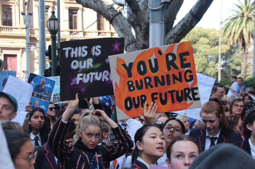 """A group of students in school uniforms hold signs, including two that read """"this is our future"""" and """"you're burning our future"""""""