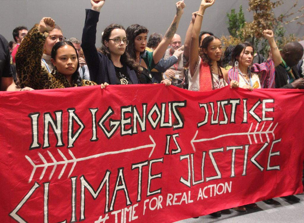 """A group of young activists raise their fists while holding a banner reading """"Indigenous justice is climate justice. Time for real action"""""""