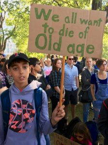 """A young person holds a sign reading """"we all want to die of old age"""""""