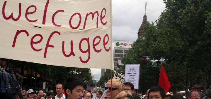 "Activist crowd holds ""welcome refugee"" banner"