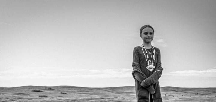 Climate change activisit and environmental icon Greta Thunberg stands alone on a hill
