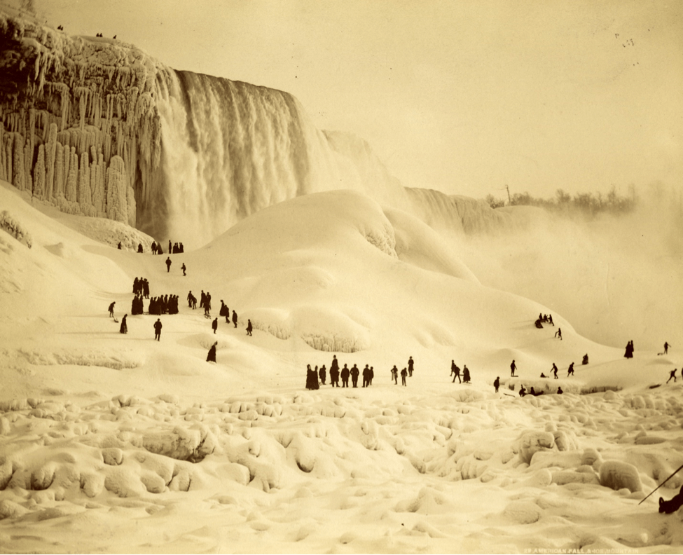 A black and white photograph of a frozen Niagara Falls with people gathering below, early nineteenth century