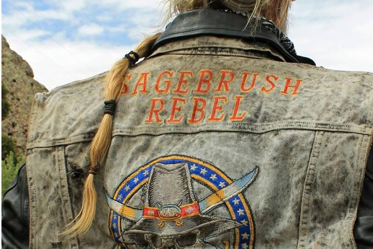 """Close up person wearing denim jacket that says """"Sagebrush Rebellion"""""""