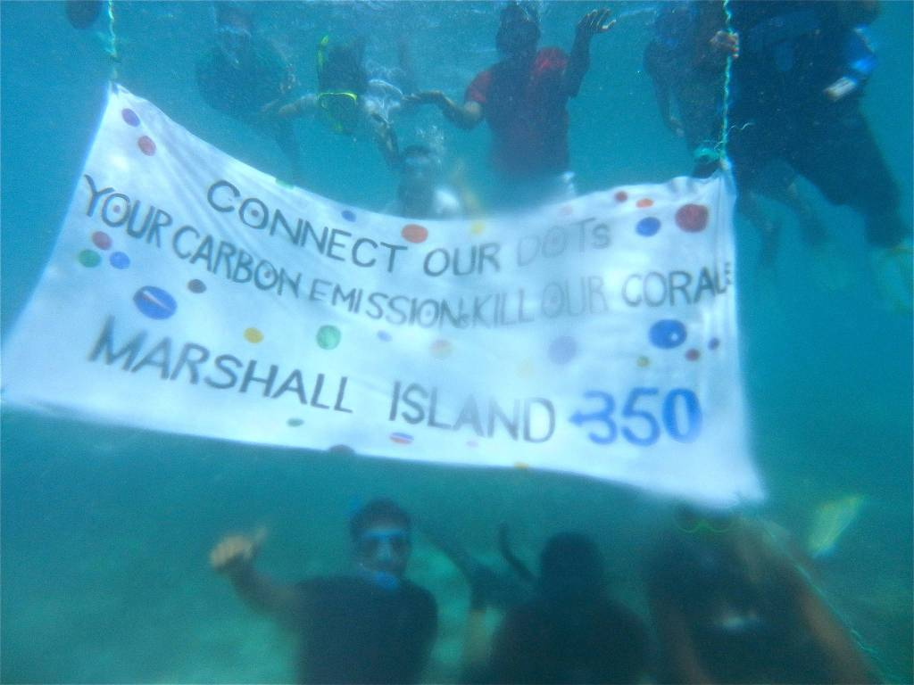 """Activists hold up a banner under the sea to protest against carbon emission. It reads: """"Connect our Dots: Your Caron Emissions Kill Our Coral"""""""