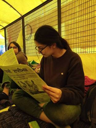 Young woman wearing glasses reads a newsletter