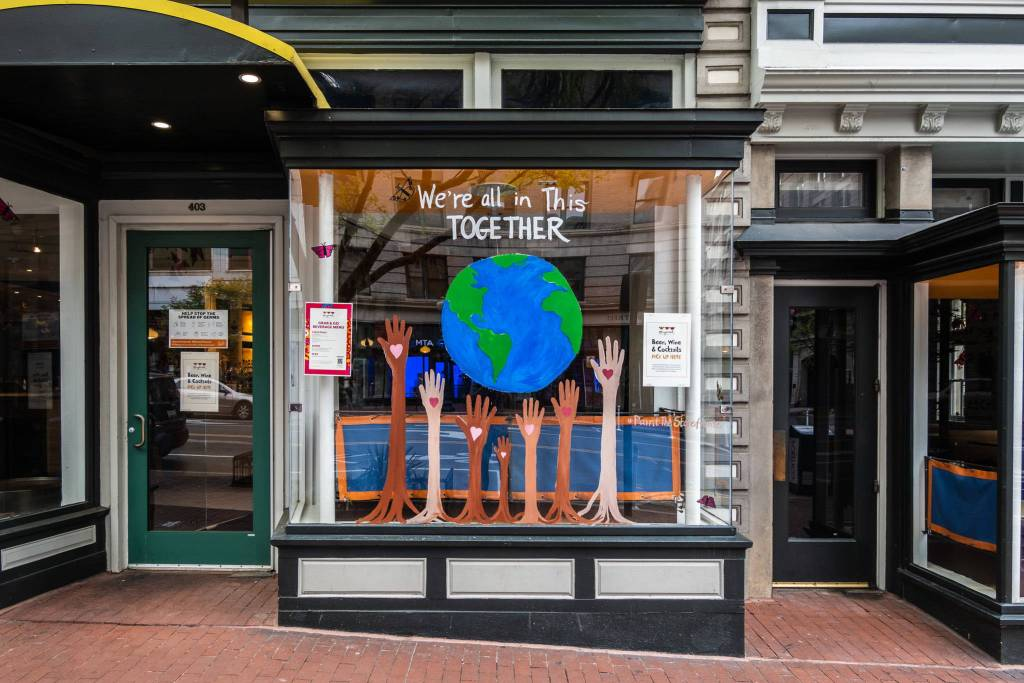 Storefront decoration showing a painting of planet earth and raised arms underneath