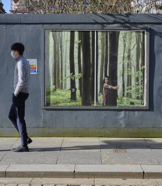 A man wearing a face mask during the COVID-19 pandemic walks in front of a poster of a young girl hugging a tree in a forest.
