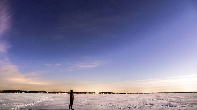 A lone figure stands on a frozen lake looking up at a cloudy blue sky.
