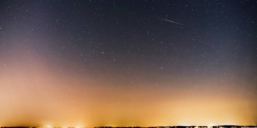 Astrophotography of Jupiter and Saturn sitting close together in a star filled sky. Lights from the city obscure the bottom part of the image.