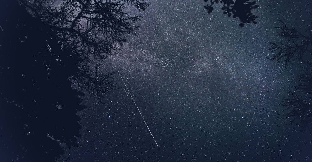 Astrophotography of a starry sky pierced by the straight white line of a Taurid meteor.