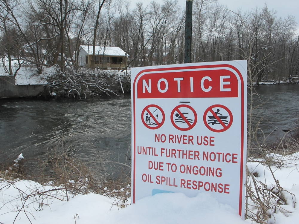 """A snowy sign beside a river indicates people should not fish, swim, or canoe, reading, """"Notice: No river use until further notice due to ongoing oil spill response."""""""