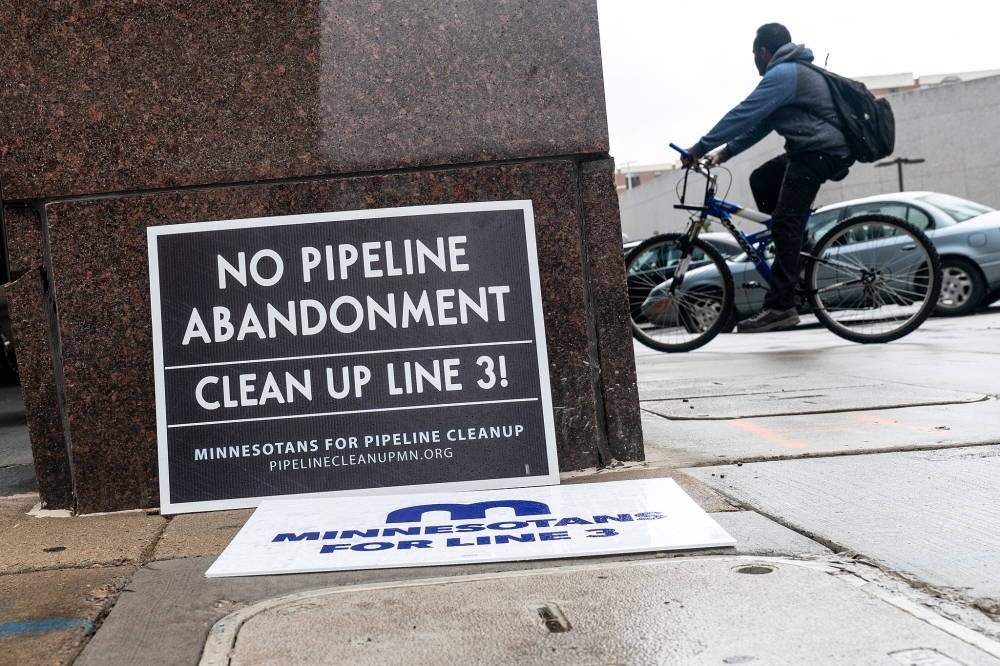 """A sign leans outside a building, reading """"No Pipeline Abandonment. Clean Up Line 3!"""""""