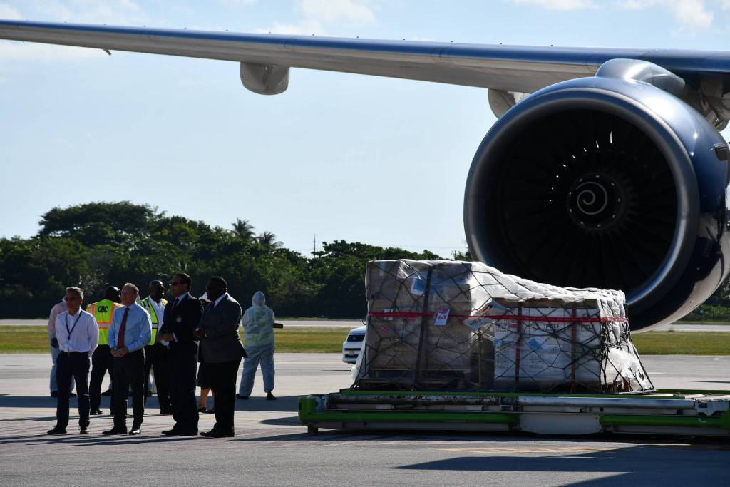 In front of an airplane engine, cargo containting Covid-19 vaccines is being uploaded