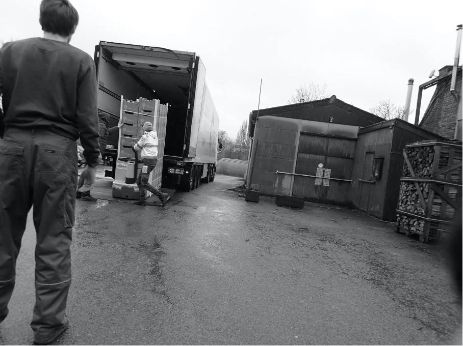 Black and white photograph of workers unloading crates of oranges from a truck