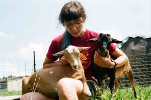A seated woman holding two young goats